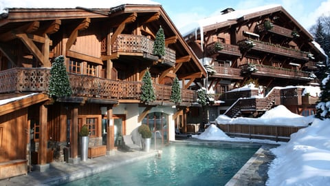 Image of hotel with outdoor pool surrounded by snow