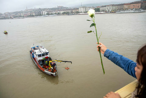 A woman throws a flower from the Margaret Bridge during a search operation on the River Danube in Budapest, Hungary.