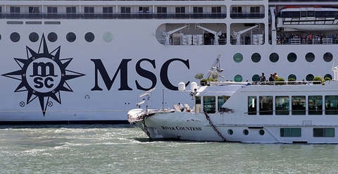 The MSC Magnifica cruise ship passes by the tourist boat, foreground, bottom right, that was struck by a towering cruiser, foreground right, in Venice, Italy.