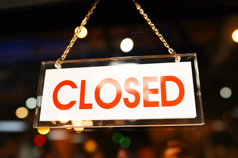 Closed sign in the window of a bar