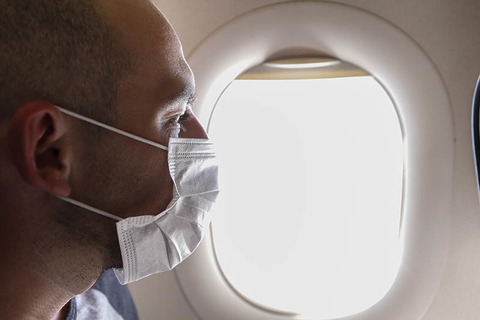 Man on airplane with mask