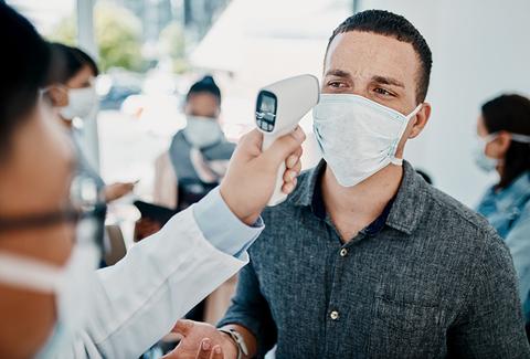 man getting temperature taken at airport
