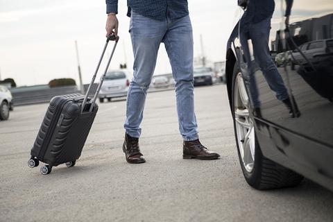 man with luggage walking to rental car