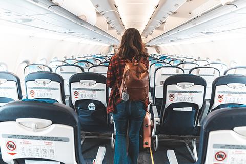 woman walking down plane aisle