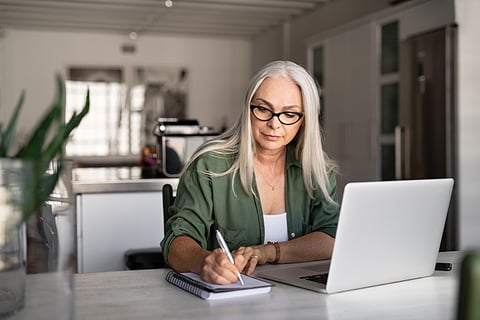 woman taking notes and using laptop