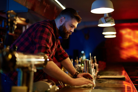 Bearded barman cleaning bar