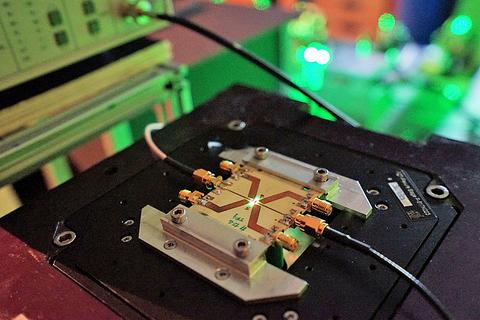 Researchers at IMO-IMOMEC have created electrically readable qubits out of artificial diamond. The photographs show a diamond quantum device mounted on a microwave (MW) board for qubit addressing under pulsed green laser illumination providing spin initialization.