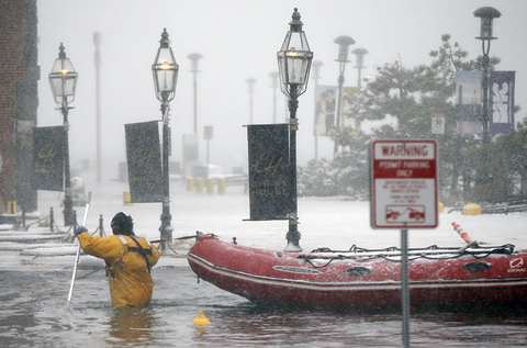 A Boston firefighter wades through flood waters from Boston Harbor on Long Wharf in Boston.