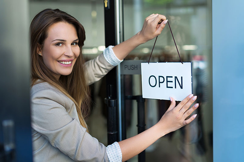 Woman hanging an open sign on a small business
