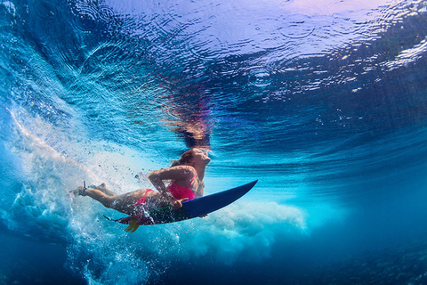Surfer diving underwater with surf board