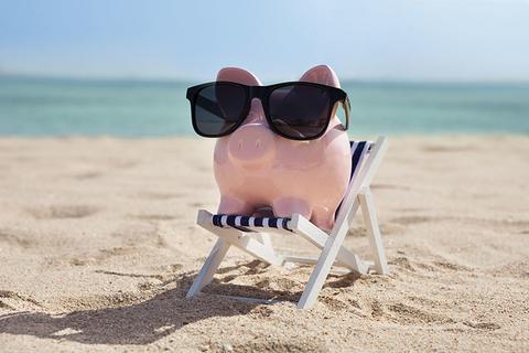 Piggy bank wearing sunglasses on a beach