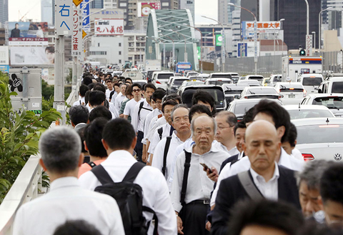 People walk on a bridge while train and subway service were suspended to check for damage after an earthquake in Osaka, western Japan.