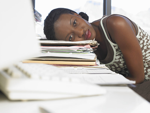 Woman leaning on desk piled with papers
