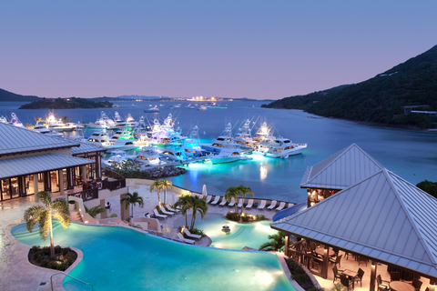 A view of the tiered infinity pools and marina at dusk
