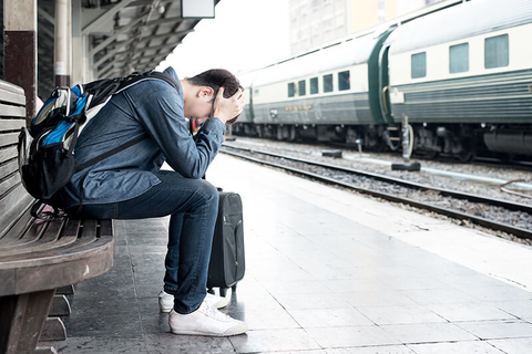 stressed traveler with head in hands outside at a train station