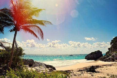 Sun shining down on a beach between cliffs in Cancun Mexico
