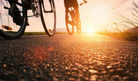 Bike wheels close up image on asphalt sunset road