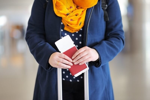 A woman holding a passport and plane ticket.