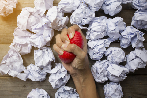 Stress ball squeezing surrounded by crumpled paper
