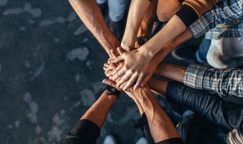 Hands on top of hands symbolizing teamwork