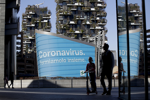 "A man and a girl in Lombardy in front of an advertisement reading in Italian ""Coronavirus let's stop it together"" //"