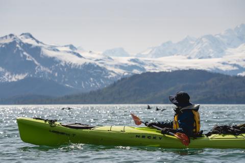 Image of kayaker looking over at mountain range