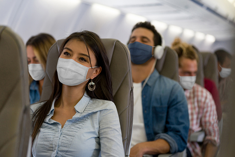 People on an airplane wearing masks