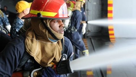 A fireman holding a firehose that is open and expelling water