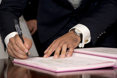 Man in suit signing his name to a book