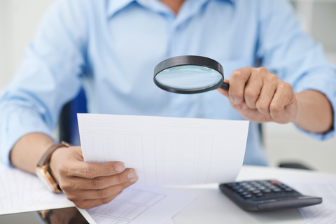 Man using magnifying glass to look at paper
