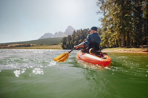 Old man paddling a kayak on a summer day