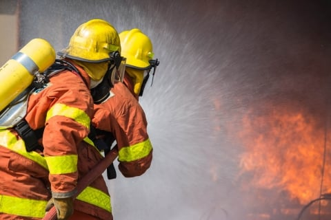 Firefighters training a hose on a fire