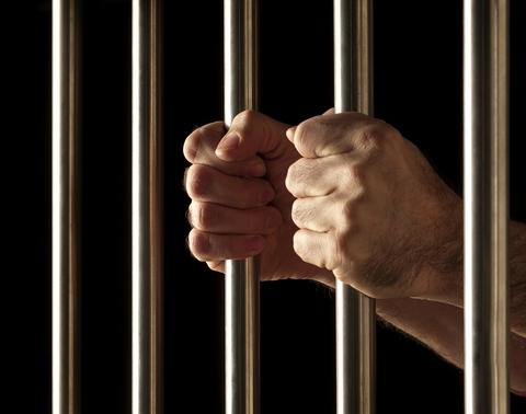 Hands clutching prison bars