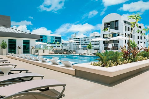The rooftop pool area at AC Hotel San Juan Condado includes a deck with poolside service.