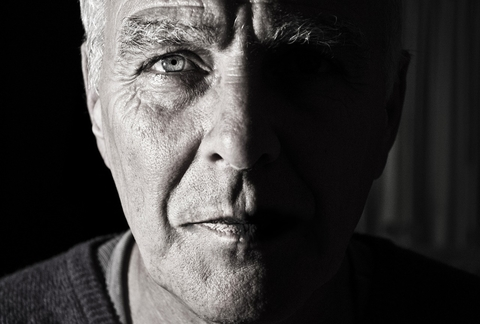 Black and white photo of old man half of face in shadow