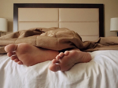 Feet poking out of sheets on bed