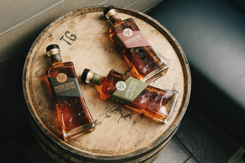 Rabbit Hole Distilling Co. whiskey bottles on a barrel - Falling Down the Rabbit Hole to Modernize Bourbon
