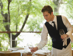 A waiter setting a table