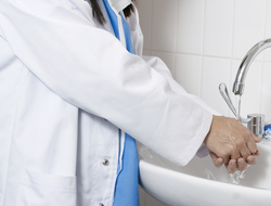 Healthcare worker in white lab coat and surgical scrubs washes his hands in sink