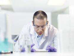 A man wearing a lab coat, purple medical gloves and eye protection