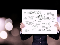 Picture of someone holding a poster board with the word Innovation and doodles depicting ideas, brainstorming.