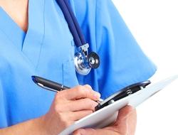 Nurse wearing blue scrubs takes notes