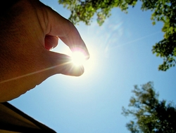 A hand that is positioned in front of the sun, as if pinching it