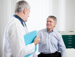 Doctor wearing a white lab coat talks to patient in office