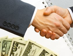 Two people shaking hands with money in the background