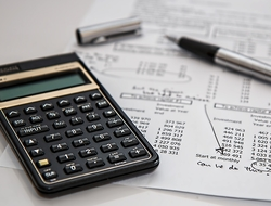 Calculator and pen on top of financial spreadsheet