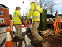 two utility workers setting up a fiber cabinet on a sidewalk