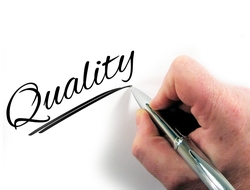 Photo of hand holding a pen writing the word quality
