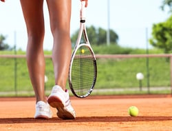 Female tennis player legs walking away on a court