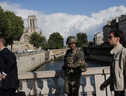 A soldier patrols on a bridge after a man attacked officers with a hammer outside Notre Dame cathedral, seen in the background, in Paris, France